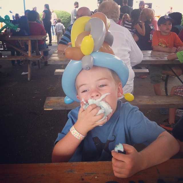 Malone wears a balloon hat and eats cotton candy at the Westfield Fair