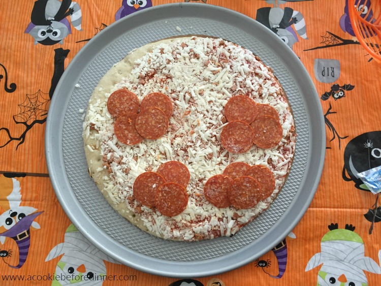 To make mummy pizza, first start with a frozen pizza!